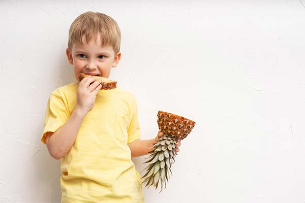 Ребенок ест ананас